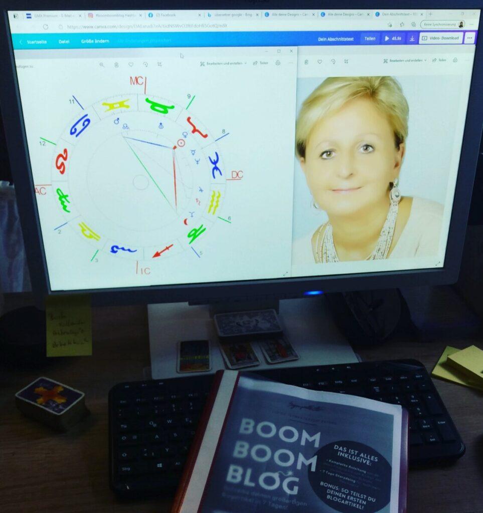 Heike Untermoser am Schreibtisch mit Bildschirm, darauf zu sehen ist ein Horoskop und ein Bild von mir. Eine Tastatur, Tarot Karten und das Workbook von Boombommblog liegt auf dem Tisch.